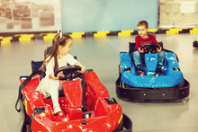 Boy And Girl Driving Race Bumper Cars In Autodrom Indoors