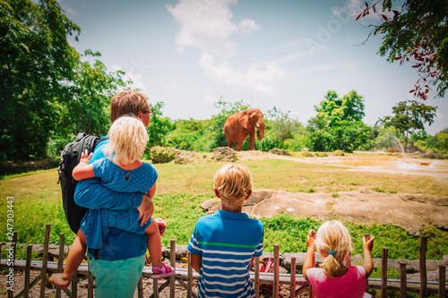 father and kids looking at elephants in zoo