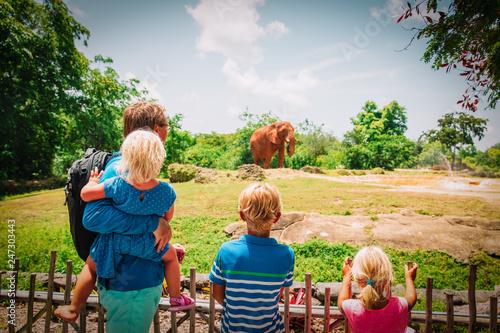 Naklejka premium ojciec i dzieci patrząc na słonie w zoo