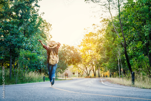 Asian woman backpack on the road and forest background, journey and traveling on holiday concept .