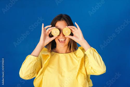 Fotografía  Portrait of laughing brunette in yellow blouse holding slices of lemon