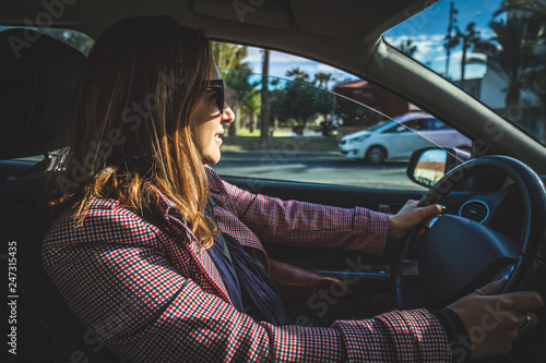 Girl driving her car on sunny day  Woman holding the serious