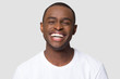 Leinwandbild Motiv Cheerful happy african millennial man laughing looking at camera isolated on studio blank background, funny young black guy with healthy teeth beaming orthodontic white wide smile head shot portrait
