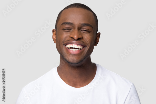 Cheerful happy african millennial man laughing looking at camera isolated on studio blank background, funny young black guy with healthy teeth beaming orthodontic white wide smile head shot portrait