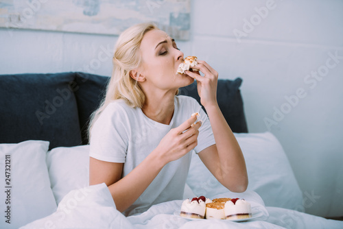 stressed woman in pajamas eating sweet cake in bed alone