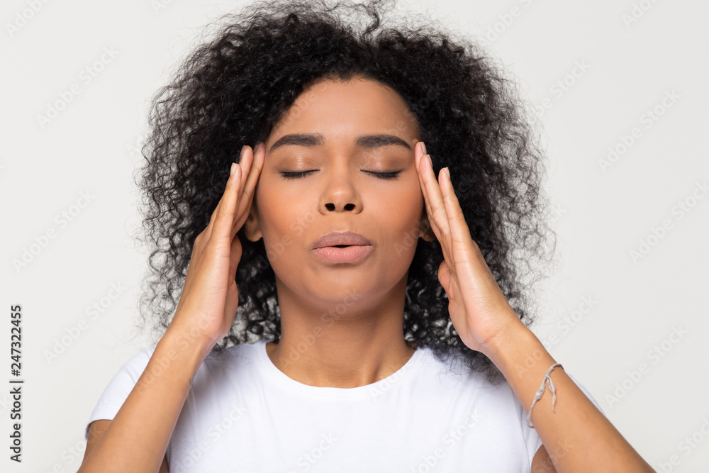 Fototapety, obrazy: Nervous african woman breathing calming down relieving headache or managing stress, black girl feeling stressed self-soothing massaging temples exhaling isolated on white grey studio blank background