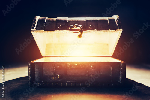 Fotografia  Ancient wooden box with glowing light.