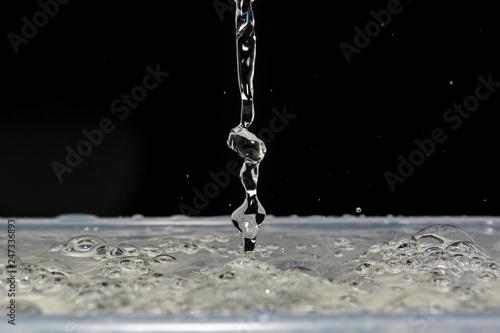 Foto auf Leinwand Wasserfalle Photo of water drops falling on water and splash on black background