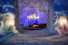 Burth Of A Jesus Installation Inside Of Snow Igloo House With Colorful Icy Plafonds And Burning Candles