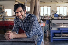 Craftsman Smiling While Leaning On A Bench In His Workshop