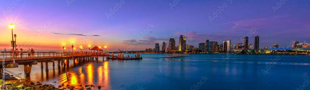 Fototapeta Panorama of Coronado old pier reflecting on in San Diego Bay from Coronado Island, California, USA. San Diego cityscape skyline with Downtown and Waterfront Marina District at twilight on background.