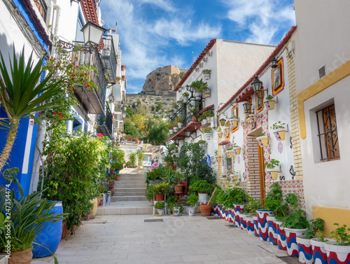 Photo Street with beautiful houses and flowers in the old city of Alicante on a sunny