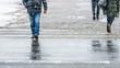 Leinwanddruck Bild - Winter City Slippery Sidewalk. Feet of people walking along the icy snowy pavement in crosswalk in snowfall. Pair of shoe on icy road in winter. Abstract empty blank winter weather background.