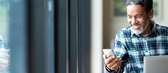 Banner of happy mature asian or hispanic old man looking at smartphone smiling positive in casual lifestyle with digital technology of older or senior guy concept. Urban elderly asian retired man.