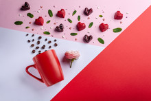 Mug, Coffee Beans, Pink Rose And Chocolates Candy Hearts Shaped, Top View. Valentines Day Romantic Greeting Card, Creative Flat Lay Sweets Food And Mint Leaves Composition