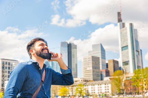 Fotografie, Obraz  Young man talking on the phone in Frankfurt
