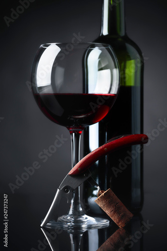Red wine with corkscrew on a black background.