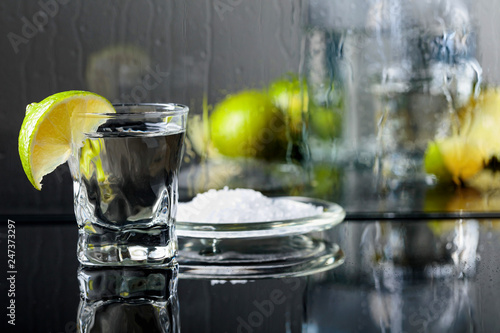 Glass of tequila with lime and salt on the black reflective background.