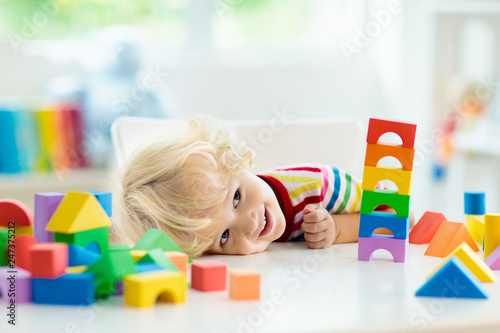 Photo  Kids toys. Child building tower of toy blocks.