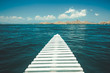 Close-up white pier leading to the ocean. Komodo island, Indonesia. Amazing marine scene. The cloudy sky over the crystal clear water. The romantic road into the distance. The conceptual image.