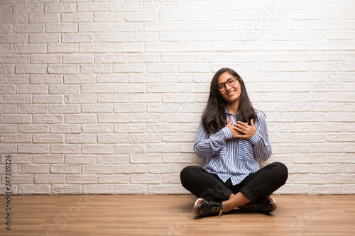 Fototapety, obrazy: Young indian woman sit against a brick wall doing a romantic gesture, in love with someone or showing affection for some friend