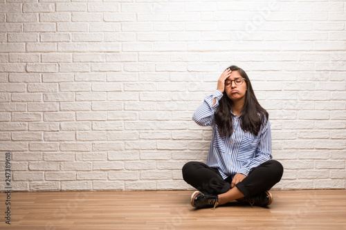 Fototapety, obrazy: Young indian woman sit against a brick wall worried and overwhelmed, forgetful, realize something, expression of shock at having made a mistake