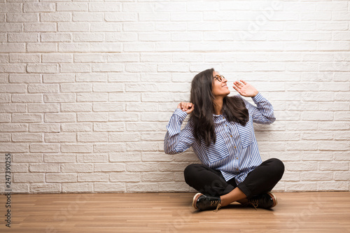 Fototapety, obrazy: Young indian woman sit against a brick wall Listening to music, dancing and having fun, moving, shouting and expressing happiness, freedom concept