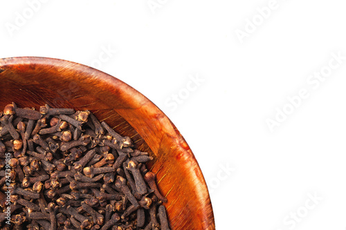 Fotobehang Kruiderij Cloves in brown wooden bowl isolated. Empty copy space for text design white background.