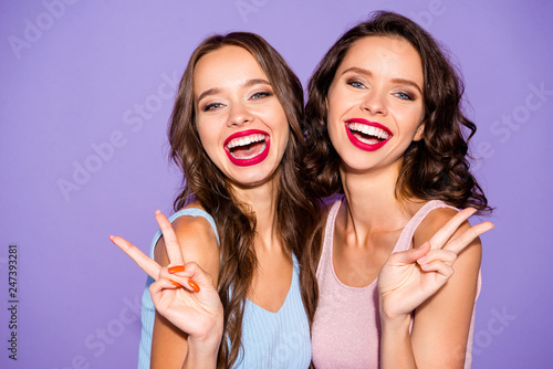 Fototapeta Close up portrait two curly stunning beautiful she her lady excited sisters bright pomade suits white teeth show v-sign say hi wear festive dresses isolated purple violet vivid vibrant background obraz