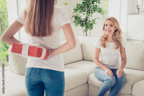 Close up back behind rear view photo unexpected two people mum and teen daughter holding hands arms behind back gift box surprise wear white t-shirts jeans in bright kitchen sit on cozy sofa