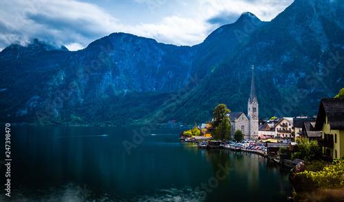 Dramatyczna sceneria wieczorna wysokich gór skalistych i miasta Hallstatt nad szerokim jeziorem
