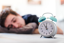 Alarm Clock In The Morning. Young Man Sleeps In The Blurry Background.