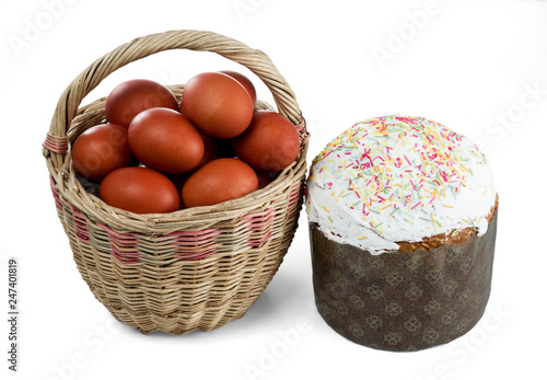 Easter wicker basket with kulich and dyed red Easter eggs isolated on a white background.