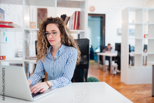 Young female accountant working on laptop in bright work station.
