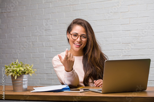 Photo Portrait of young student latin woman sitting on her desk inviting to come, conf