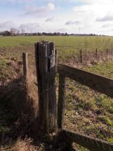 Ein Zaunpfahl Aus Verwittertem Holz Umwickelt Mit Draht An Einem Gatter.