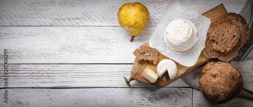 French goat cheese with cereal bread and pear on white wood background. Space for text, top view