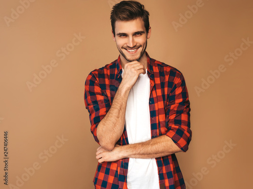Portrait of handsome smiling stylish hipster lumbersexual businessman model dressed in red checkered shirt Tablou Canvas