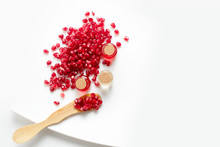 Pomegranate Oil In A Bottle And Pomegranate Seeds On A White Background