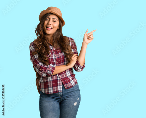 Cuadros en Lienzo Full body young traveler curvy woman pointing to the side with finger