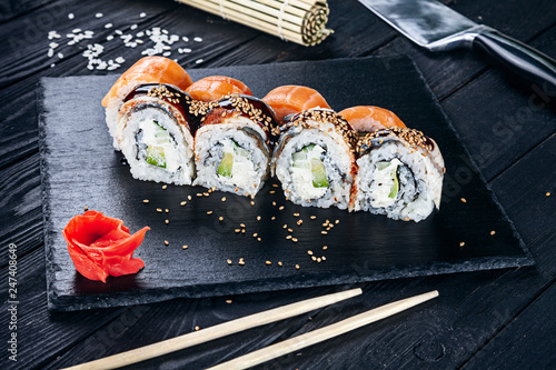 Poster Sushi bar Served sushi rolls on black stone with chopsticks. Close up view on sushi on dark background. Traditional japanese cuisine. Restaurant, food menu, recipe, cafe concept. Lifestyle with copy space
