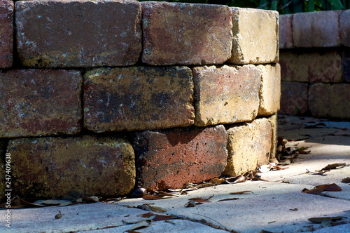 Foto  Low angle view of curved brick wall of well, half in sunlight, half in shade