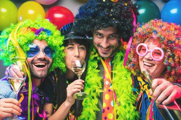 Lachende Freunde in bunten Kostümen trinken Sekt bei einer Karneval party .