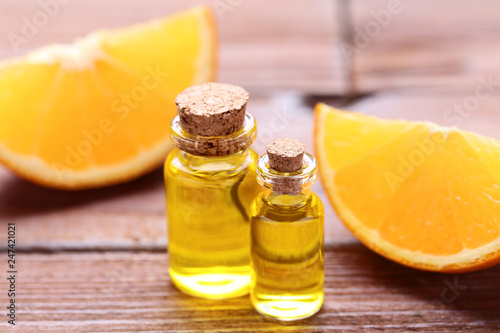 Fotografía  Orange oil in bottles on brown wooden table