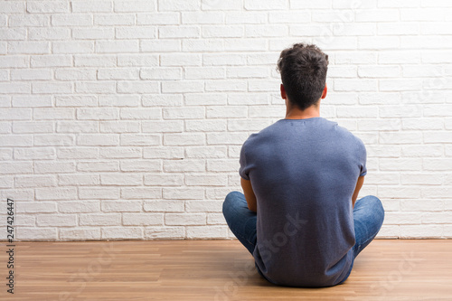Fototapeta Young natural man sit on a wooden floor showing back, posing and waiting, looking back obraz