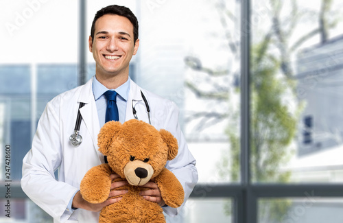 Fotografia  Handsome young pediatrician portrait holding a teddy bear