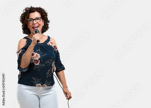 Fototapety, obrazy: Middle aged woman happy and motivated, singing a song with a microphone, presenting an event or having a party, enjoy the moment