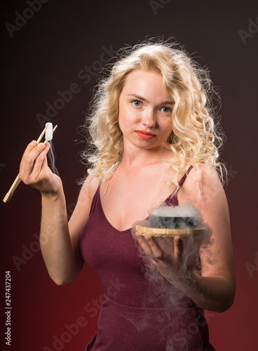 Fotografía  Beautiful woman with blonde long curly hair holds chopsticks and eats
