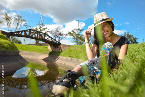 Fotografie, Obraz  Mujer joven sentada junto al lago sonríe mientras sostiene su sombrero con picar