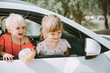 Funny little girls sticking heads out car window. Traveling by car with kids concept .